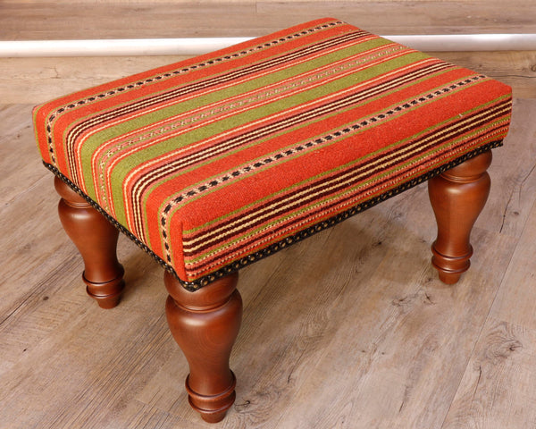 Theses Turkish Kilim stools often uses salvaged pieces.  This use produces an interesting look with the pattern being offset rather than centred, making the pieces unique and different. On this occasion the stool has a stripy design going across the length of the stool.  The bands vary in width.  The colour palette used is striking with lime green, bright orange, deep red. black and cream.