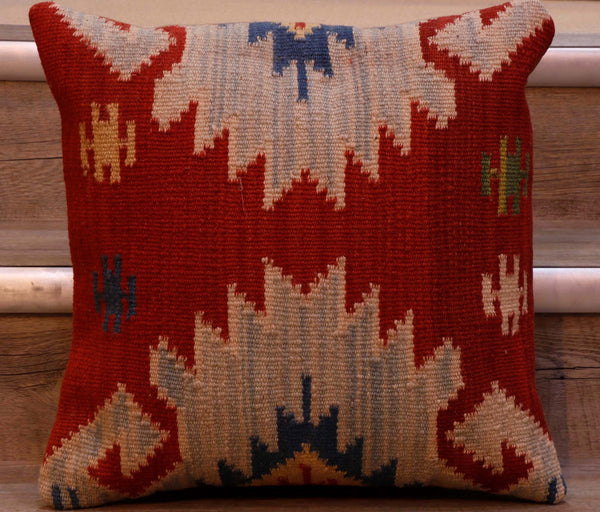 This Turkish kilim cushion measuring 40 by 40 centimetres has a brick red ground with two facing half medallions pointing to the centre in shades of blue with yellow and red central highlights.  A few smaller motifs in blue, yellow, cream and green can also be found.  The back of the cushion is usually Faux suede or cotton.