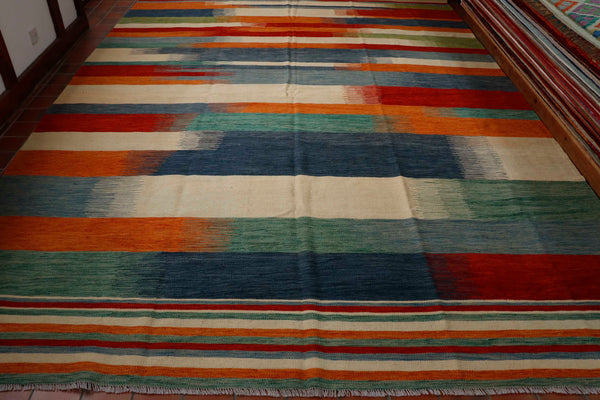 Size 407 by 286 centimetres.  Such great colours in this modern style Afghan kilim. They conjure up images of the seaside with bands of colour going across the rug broken down blended together into third sections across much of the it consisting of various shades of blues, teal, cream, green, red and terracotta, shades of the Mediterranean even.