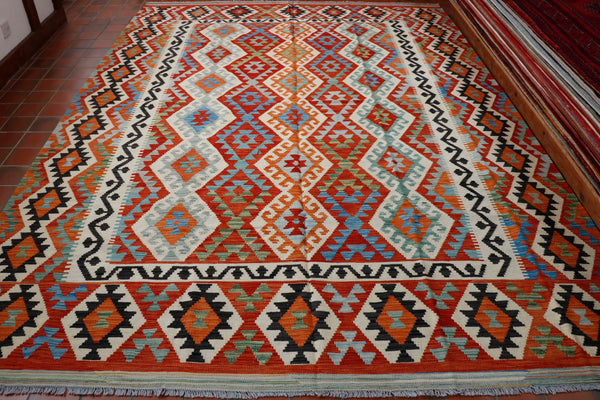 A very large Afghan Kilim produced fro wool gained from indigenous sheep. The piece is very striking using quite a lot of black which contrast beautifully against the terracotta orange blue and green.