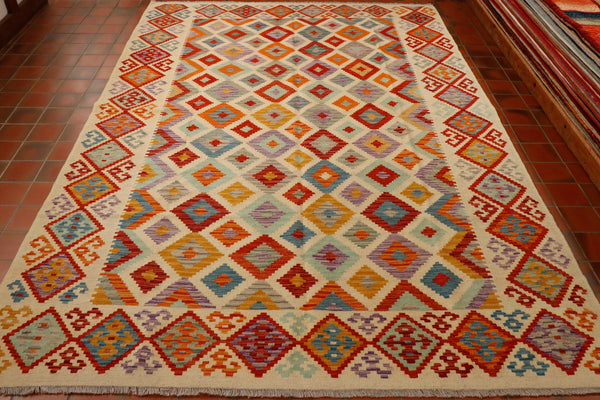 Large Kilim rug 306 by 204 centimetres.  The oatmeal background keeps the rhombi pattern overall quite light in appearance and the design is smaller and therefore not so bold.  Colours used are oatmeal, terracotta, old gold, lilac, duck egg blue and soft grey.  With the border consisting of larger rhombi in red with colour inserts.
