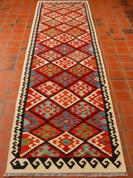 This striking Afghan Kilim runner is a mix of wonderful colours that really bring it to life and make it sing. The outer border is oatmeal colour with a deep navy pattern which really stands out and frames the runner. The inner planner is covered with large diamonds in colours of flame orange, mid blue, olive green and turquoise. In this photograph the runner is sitting on terracotta tiles and looks really great.