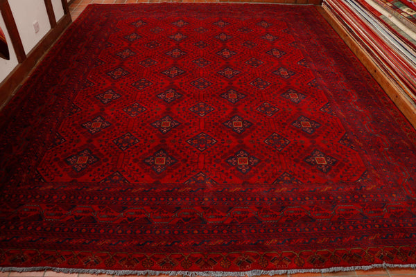 This Karl Mohammadi is 381 by 300 centimetres. A wonderful rich, raspberry red background carpet in a traditional design. This particular piece has 12 borders with an ornate floral pattern in dark blue and gold.  The central section is laid out in an even pattern with larger stylised flowers again in deep blue with gold highlights.