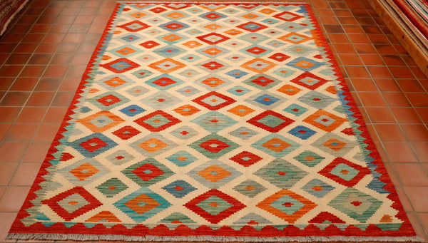 This Afghan kilim has been made using traditional methods but they have given the colour and design a more contemporary look and feel. The background is cream with a brick red edge and the all-over diamond design is in terracotta, duck egg blue, sea green and a soft grey.  There is a strong band of red as a border, over laid with triangles encasing the main design.