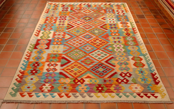 This Afghan kilim is a kaleidoscope of colours which include oatmeal, terracotta, turquoise, apple green, gold, tangerine, duck egg blue, mink, denim blue, heather and sea green.   There are several border bands of varying widths the outer being hooks.  The next band in made up of hexagons and the inner a further cross based geometric design. All of these are in the same colour palette. It might have been easier to describe which colours were not in it!!!