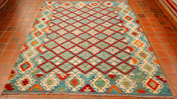 The main background and border colour is a denim blue with brick red, turquoise, olive green and cream to make up the geometric pattern, there are also small amounts of tangerine used.  Using the brick red to outline the diamond motifs creates almost a trellis effect.  The border to this rug has connecting diamonds, encased in hooks in cream on the blue background.