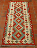 Handwoven Afghan kilim runner in strong terracotta, cream and green/blue shades.  The design upon it is a series of bold diamonds through the main length of the runner with a contrasting geometric hook design upon the border.  An inner border with smaller contrasting diamonds on a cream ground lightens this piece,