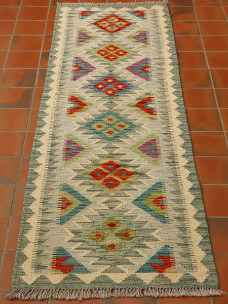 This kilim runner has a muted palette using soft sea greens, creams, lime greens, heathers with the occasional orange to highlight.  The main area is a series of triangles and diamonds going through the centre, length ways.  There is a border made up of greens and creams.  Smaller diamonds are found within the larger ones using contrasting colours.