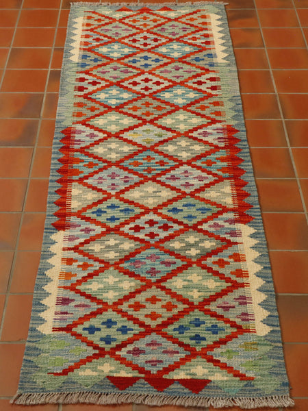 Multiple shades of blue have been used in this Afghan kilim runner, including pale denim, duck egg, mid blue and turquoise, along with soft green, poppy red and touches of heather.  The main part of the runner consists of interlocking diamonds, each with a contrasting 4 smaller crosses within.  Each edged in red.  The border is blue, with a geometric pattern upon it, using triangles using the same colour palette as a contrast.