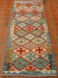A traditional geometric Afghan kilim runner in really soft shades of blue, terracotta, cream, green, pink and duck egg blue.   The main body of the runner is a series of diamonds, each using the same colour palette with a decorative motif inside each one.  The border is blue to the edge with a coloured hook pattern upon it.