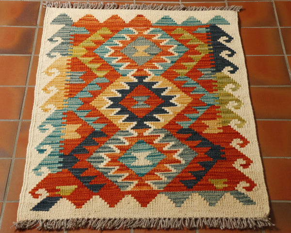 A small mat with 3 diamonds across the main ground with a striking orange, sea green, dark blue, yellow and cream palette.  The edge is a cream hook pattern.