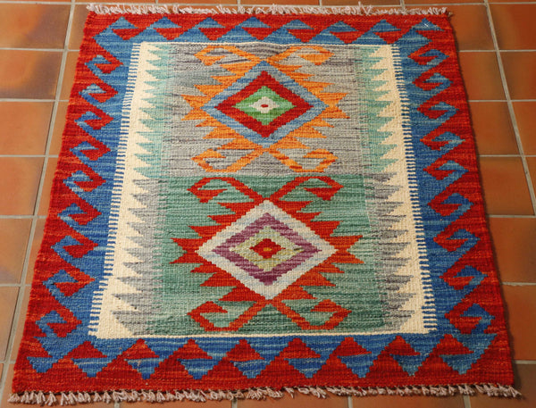 A small mat with 2 diamonds with a striking orange, sea green, blue and cream palette.  Around the edge is a geometric pattern using a combination of all the colour palette.  This being a mix of orange, red, duck egg blue, grey and another bold blue tone.  The edge has a bold red/orange hook decoration on the border.