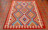 The rich poppy red contrasts well with the light bright blue, terracotta, cream and soft heather colouring.  The central design is that of three main bands of connecting diamonds going down the length of the rug.  The border houses a cream geometric pattern.