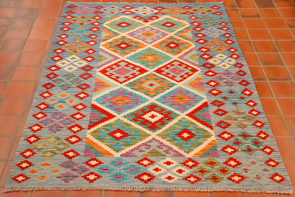 This lovely kilim has quite a wide border in pale blue with small diamonds throughout. the main panel in the centre is covered in larger diamond shapes in colours of flame red, terracotta, strong turquoise, cream, both olive green and sea green, heather and even some duck egg blue.