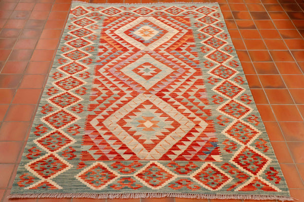 A lovely kilim with slightly softer tones than most of the Afghan kilims. The outer border is a lovely blue green shade and the other dominant colour is the brick red.  The central design consists of three diamonds going down the length of the rug each housing a geometric design in a contrasting colour.  Moving out from he diamonds are a series of triangular decorative bands going to the border.  The border is decorated with interconnecting diamonds all edged in cream.