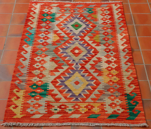 This terracotta Afghan kilim will add warmth and style to a plain room.  With a wave pattern going up either length in yellow, turquoise soft green, oatmeal and pale grey and 3 diamond shapes in the central section, a further two bands of stylized flowers on either side, all in the same colour palette.