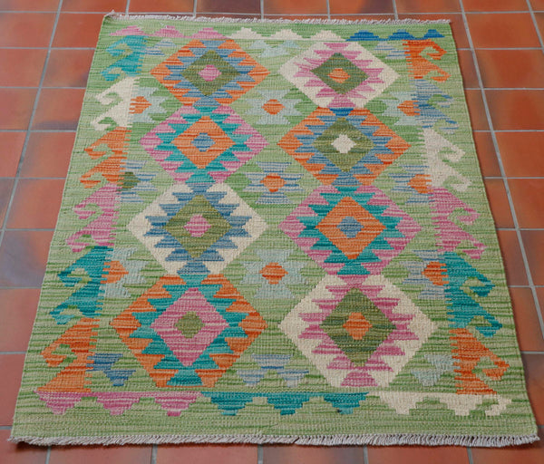 This is a very unusual colouring for an Afghan kilim.  The main colour is a very English apple green with two bands of diamonds in rose pink, with oatmeal, turquoise, blue and terracotta. The border has a hook design going up either length using the same colour palette.  This colour combination is quite mellow in comparison to most of the Afghan kilims.
