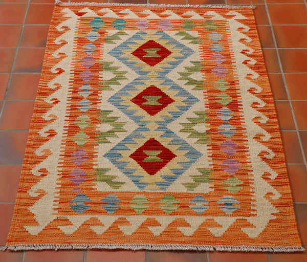 In this kilim, they have used orange/terracotta as the main colour around the hook design on the borders.  The other geometric designs , including the three central diamonds with oatmeal in the centre and pale blue, soft green, barley gold and two small diamond medallions in the middle in strong brick red.