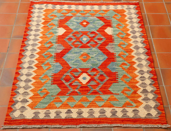 This kilim has a rich terracotta ground in the centre where you can find 4 hexagon designs.  Two are blocked in with sea blue and pale green internal designs, the other two showing the line design in mottled grey and the terracotta behind.  The border continues with this colour palette, also including orange and oatmeal.  There being a hook design and stylized flower pattern around the edge.