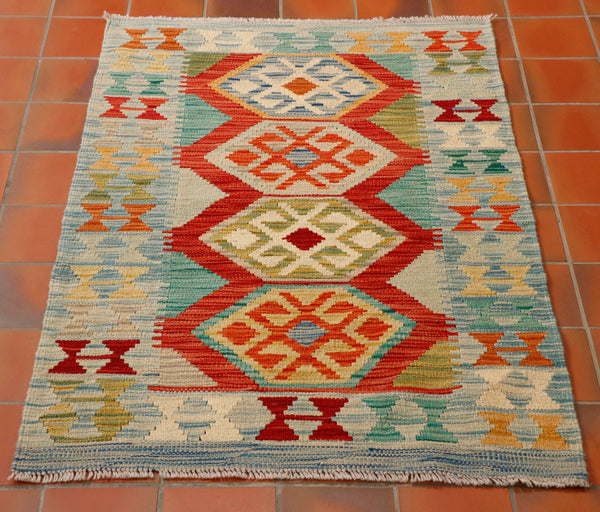 Really lovely colours used in this Afghan kilim of flame orange and duck egg blue, with old gold, red, turquoise, oatmeal and olive green. The central section contains four hexagon designs and the border a further geometric pattern.  The border has a pale blue ground with the design on top being in the same colour palette.