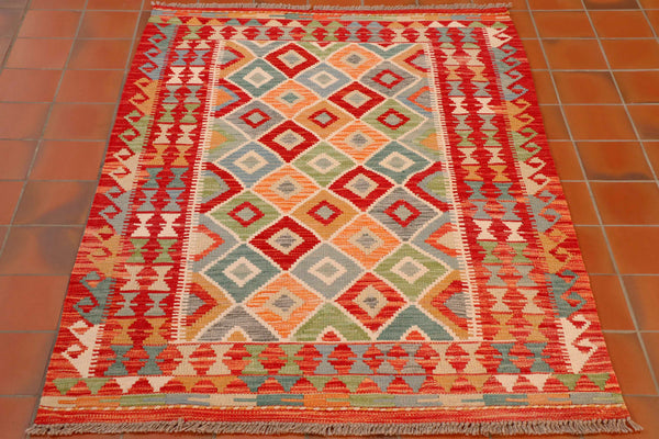 A lovely mix of colours in this pretty kilim with the main colour being a brick red with cream, tangerine, old gold, apple green, pale blue, teal and a soft grey.   There is a hook design down the length of either side of the rug, and a band of triangles on either end forming the border in the same colour palette.  The main area of the rug is made up of a symmetrical layout of diamonds, with a smaller diamond pattern within each.