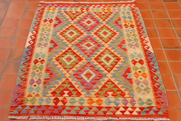 This kilim is made up of a traditional geometric design in colourings of terracotta, sandy gold, olive green, pale blue and a shade of heather/lilac. There is a hook design down the length of either side of the rug, and a band of triangles on either end forming the border in the same colour palette.  The main area of the rug is made up of a symmetrical layout of diamonds, 7 in total with a smaller diamond pattern within each.