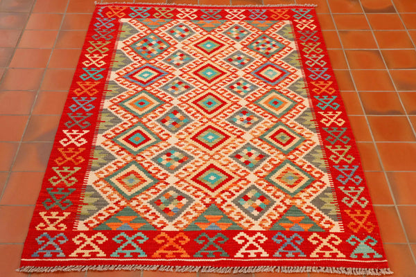 A lovely kilim in great colours which includes three different shades of green, cream and brick red.  The large central section has a diamond design upon it with a hook pattern in orange going around the edge of each diamond. The border consists of a strong red band with a geometric pattern on it using colours from the same palette.