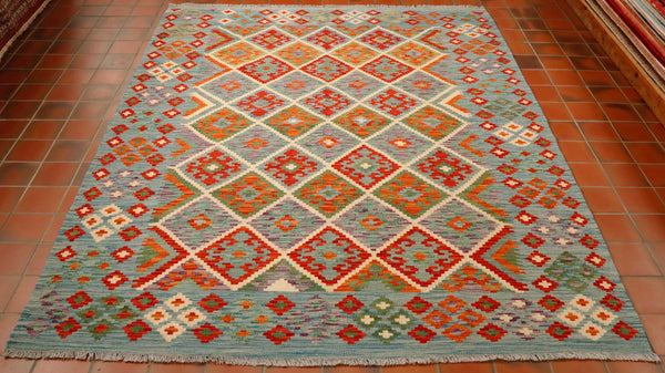 The overall lightness of this kilim gives it a more contemporary feel. The main colour is a soft blue almost grey colour with terracotta and brick red, olive green and cream.   The main area of this rug is a series of interlocking diamonds with a geometric design within each.  The border has a broad decorated band containing small geometric stylized flowers all in the same colour palette.