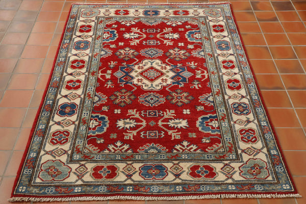 This vibrant bright kazak has a central section that is a stunning red, the predominant border has a cream ground with stylized flowers in shades of blue.  The main decoration in the centre of the rug is also a cream and blue combination.  A large central motif with stylized floral images surrounding it.