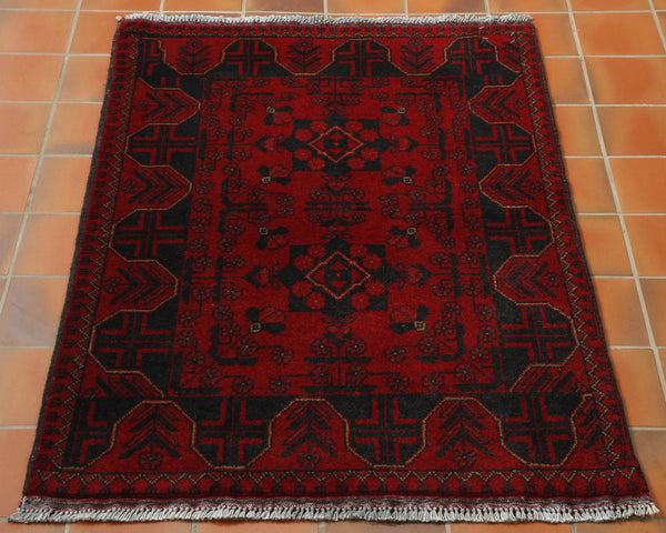 A deep red rug with dark blue geometric design.  With highlights in yellow/green.