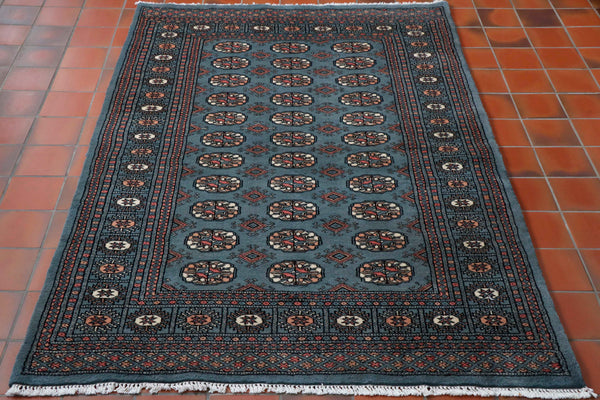 A soft blue ground with a pink, peach and cream pattern design with the highlights for the pattern work being in black.  The design is a standard classic Bokhara design.