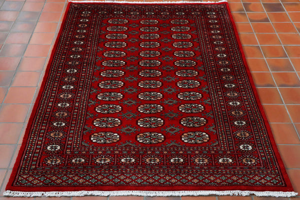 A deep red ground with a green, peach and cream pattern design with the highlights for the pattern work being in black.  The design is a standard classic Bokhara design.