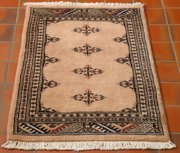 Hand-made Pakistan Bokhara rugs have a lovely silky smooth feel. Sometimes they are mistaken for silk as the wool is so soft and fine. They are hand knotted in the villages around Lahore Pakistan. The background colour of this rug is a warm beige. The design in the centre is very simple with four small diamonds running down the length of the rug. Other colours used in the rug are a soft pink and tiny touches of peach.