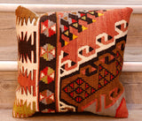 The pieces are often salvaged from old kilim so the pattern may be cut in unusual and interesting ways.  The palette for this cushion is a mix of dusky red, grey, bright red, tan, dark brown and cream.  With yellow and lime green highlights.  The design is geometric with a series of stylized flowers, feather shapes and trees.  In addition to this there are some interlocking triangles and interlocking crosses.  The back of the cushion is usually Faux suede or cotton.