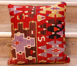 The pieces are often salvaged from old kilim so the pattern may be cut in unusual and interesting ways.  The palette for this cushion is a red ground with black, brown, mauve, orange and lime green, and cream.  The design is geometric with a series of interlocking triangles, and other geometric shapes.  The back of the cushion is usually Faux suede or cotton.