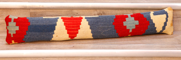 This lovely bright draught excluder is made from a salvaged piece of Turkish Kilim. It is single-faced with a faux suede/linen backing and fibre filled.  The colour palette is a cream background with triangles and geometric shapes in red, blue, yellow and grey running along it's width.