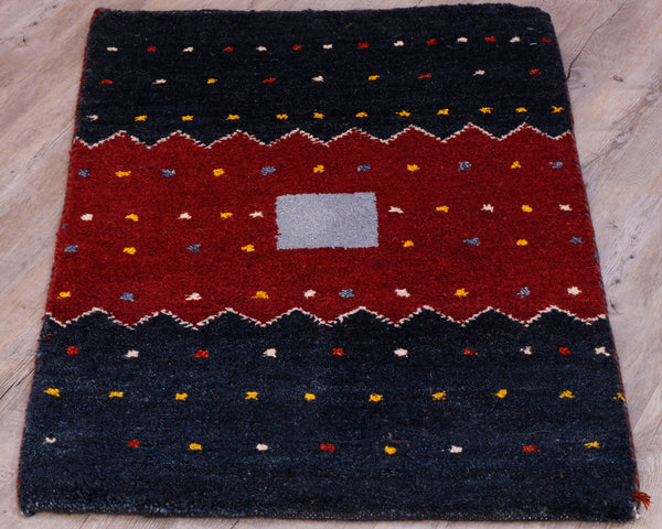 This small mat has two navy blue bands of colour on each end.  With a central red section in the middle.  There is a small grey box in the centre and a cream zigzag edge to the red band.  Over the entirety of the mat are yellow, red and cream dots.