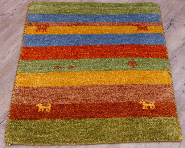 This small mat ha s striped pattern upon it.  The bands of colour go across it's width and are bright green, tan, terracotta, golden yellow, orange and blue.  There are also 4 small goats, two in orange, two yellow.