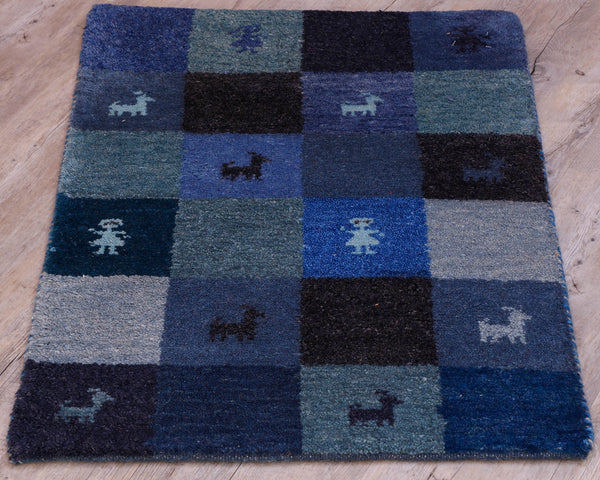 This small mat has a chequerboard design in various shades of blue.  There are 4 small people and 8 goats in some of the sections in contrasting blues.  Some of the blues have green hues.