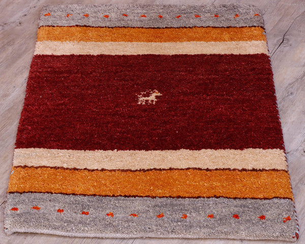 This Gabbeh mat has a braod band of dark red/burgundy vertically across the centre, edged on either side with bands of cream, followed by golden yellow/orange and then a grey band with orange dots across it.  In the centre of the red/burgundy section can be found a goat in cream.