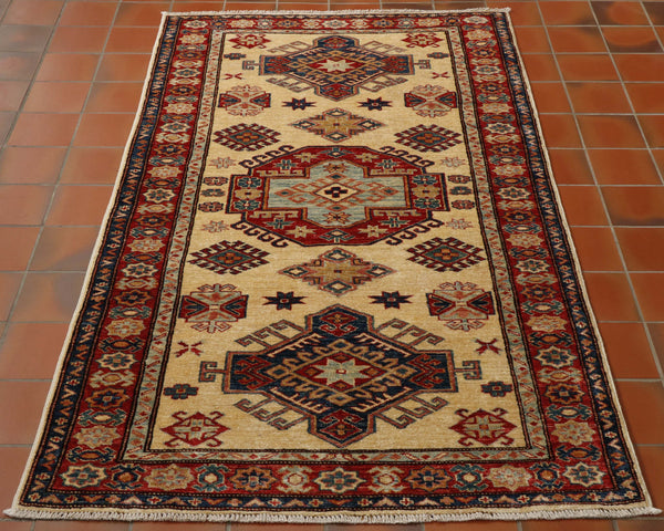 Cream coloured Kazaks are quite difficult to source.  The warm buttercream ground is contrasted wonderfully with the rich red border colour and central motifs. This Kazak is also quite narrow versus its length, which is even more unique.  In addition to the red, a range of blues and golden yellows can be found in the decoration.