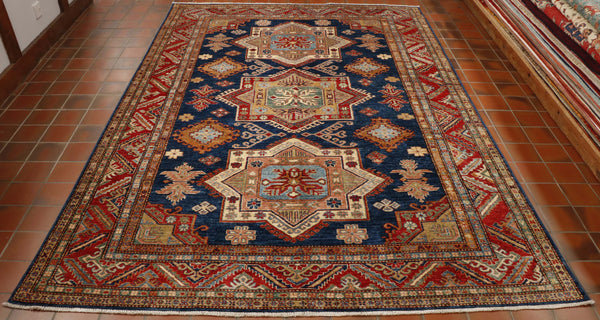 A beautiful bold geometric design which is very typical of a Caucasian design. It is an interesting carpet with three main medallions going down the length.  The colour palette consists of a dark blue ground surrounding the medallions, which consist of cream, red peach, soft green, soft blue.  It is quite a varied colour palette.  There are 5 borders of varying widths mixing geometric design with stylized flower designs.