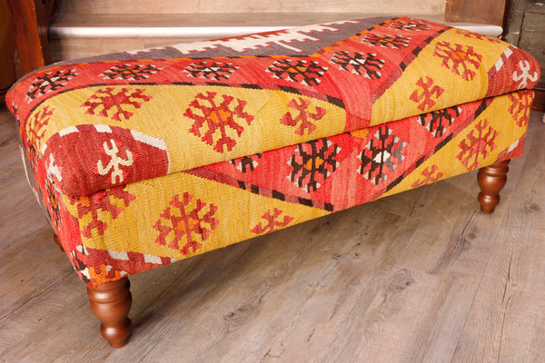 Salvaged Kilim rugs are usually used in the production of these pieces.  This ottoman has a palette of red, bright yellow, dark brown, cream and mushroom.  The design is laid out symmetrically.  With bands of colour in V formation along the length of the ottoman and a layer of almost snow flake shaped decorative motifs in contrasting colours upon them but from the same colour palette.