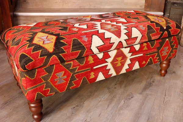 Salvaged Kilim rugs are usually used in the production of these pieces.  This ottoman has a red background to it with a dramatic geometric design upon it in dark brown, crisp ivory, golden yellow.  Each of the main geometric designs is edged in yellow, the ivory design edged in dark brown.