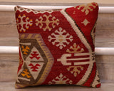 The pieces are often salvaged from old kilim so the pattern may be cut in unusual and interesting ways.  The palette for this cushion is a deep red ground, upon which can be found decoration in cream, soft green, mauve, yellow and brown.  The decoration is a series of almost snowflake shapes, some triangles and banding.  The back of the cushion is usually Faux suede or cotton.