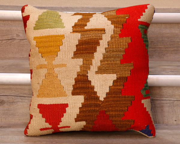 The pieces are often salvaged from old kilim so the pattern may be cut in unusual and interesting ways.  The palette for this cushion is a mix of yellows, greens, brown and red on a cream ground.  The decoration is a series of bands of broad zigzag and interlocking triangles.   The back of the cushion is usually Faux suede or cotton.