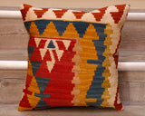 The pieces are often salvaged from old kilim so the pattern may be cut in unusual and interesting ways.  The palette for this cushion is a mix of yellows, reds, cream and blue.  The main section of the cushion is decorated with triangle based design with a band to the top and side on a cream ground with orange/red hooks and other geometric shapes.  The back of the cushion is usually Faux suede or cotton.