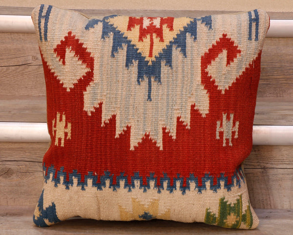 The pieces are often salvaged from old kilim so the pattern may be cut in unusual and interesting ways.  The palette for this cushion is a bright red ground upon which can be found a blue and pale blue decorative central design with a pale yellow and cream design laid upon it.  There is a border of cream along the bottom with stylized, geometric floral decoration in blue, yellow and green on it.  The back of the cushion is usually Faux suede or cotton.