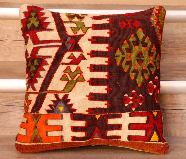 The pieces are often salvaged from old Turkish kilim so the pattern may be cut in unusual and interesting ways.   This cushion has a plum coloured background with geometric decoration upon it using contrasting colours of bright red, cream, orange, tan, with highlights of yellow and blue.   The back of the cushion is Faux suede or cotton.