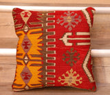 The pieces are often salvaged from old Turkish kilim so the pattern may be cut in unusual and interesting ways.  This cushion has a colour palette of a red background with a striking yellow corner section.  Overlaid is a series of geometric motifs and designs in brown, pale yellow, pinky mauve and cream. The back of the cushion is Faux suede or cotton.